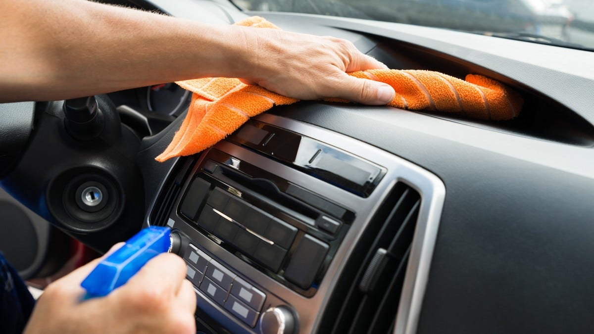 A man wiping down the interior of his car.