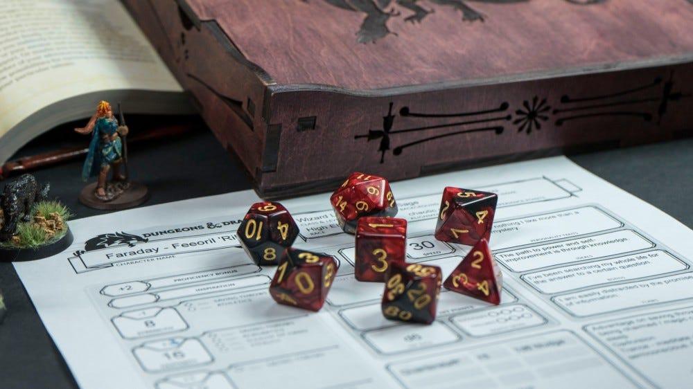 Набор красных кубиков Dungeons & Dragons в виде миниатюры и листа игрового персонажа