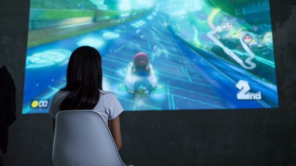 A woman playing Mario Kart on a projected screen