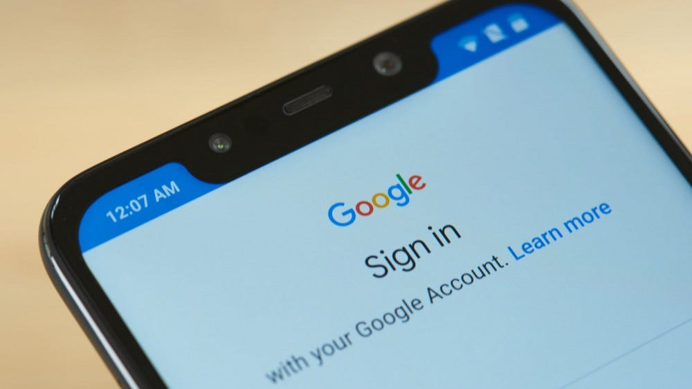 A phone showing a Google login screen.