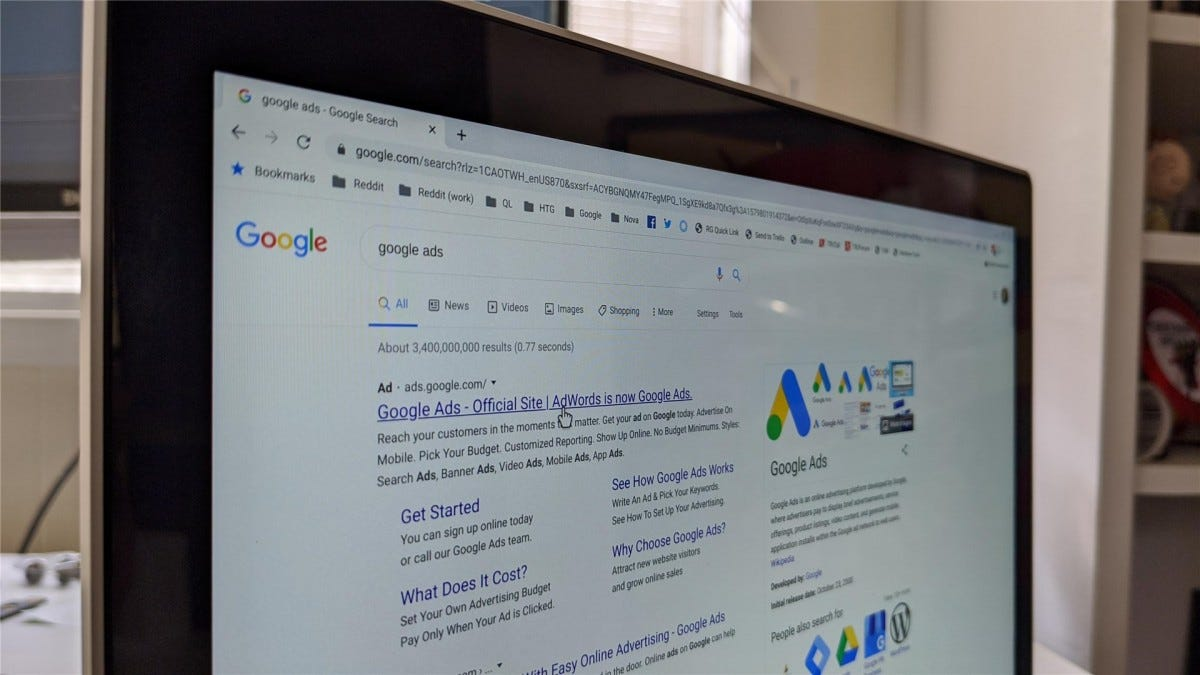 A laptop showing an ad in Google search with a cursor getting ready to click it
