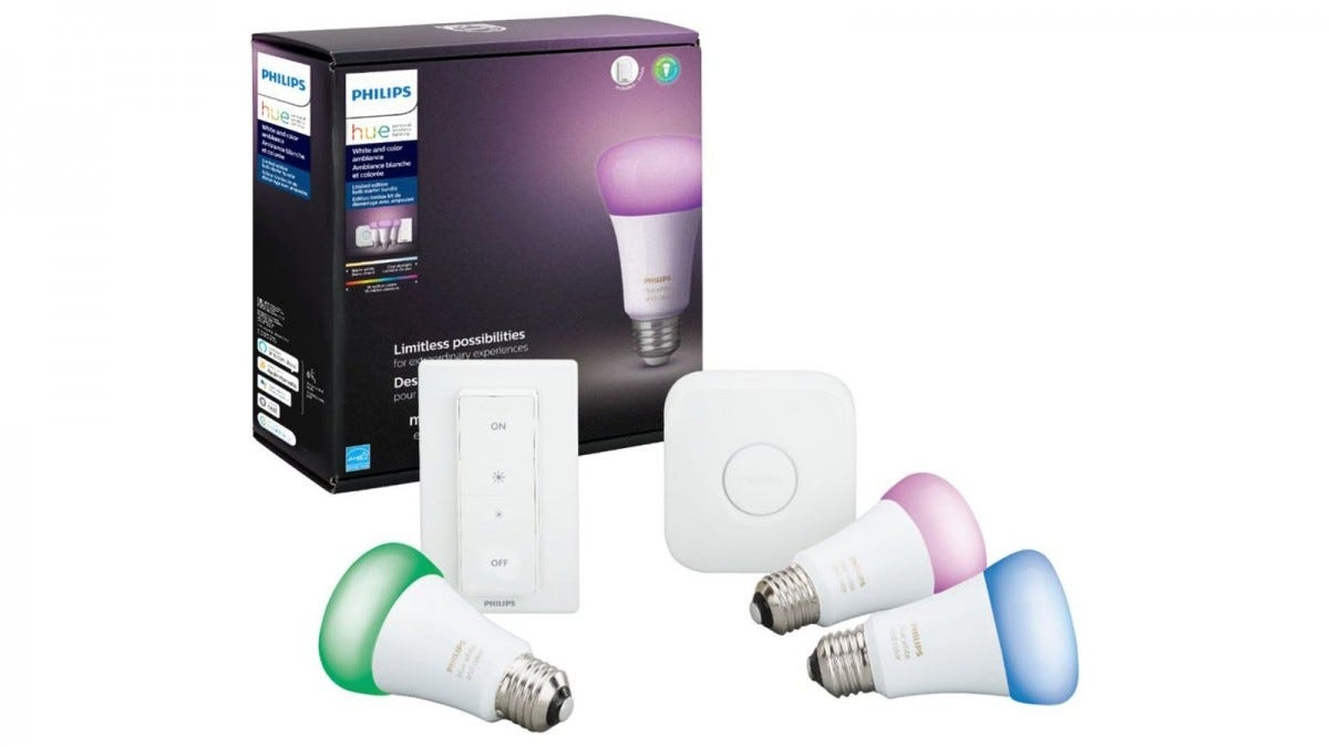 A Philips Hue Bridge, remote, and three colored bulbs.