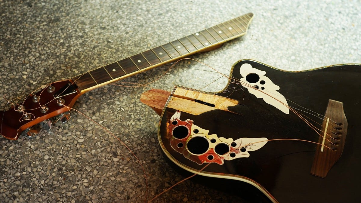 A broken guitar sitting on a counter.