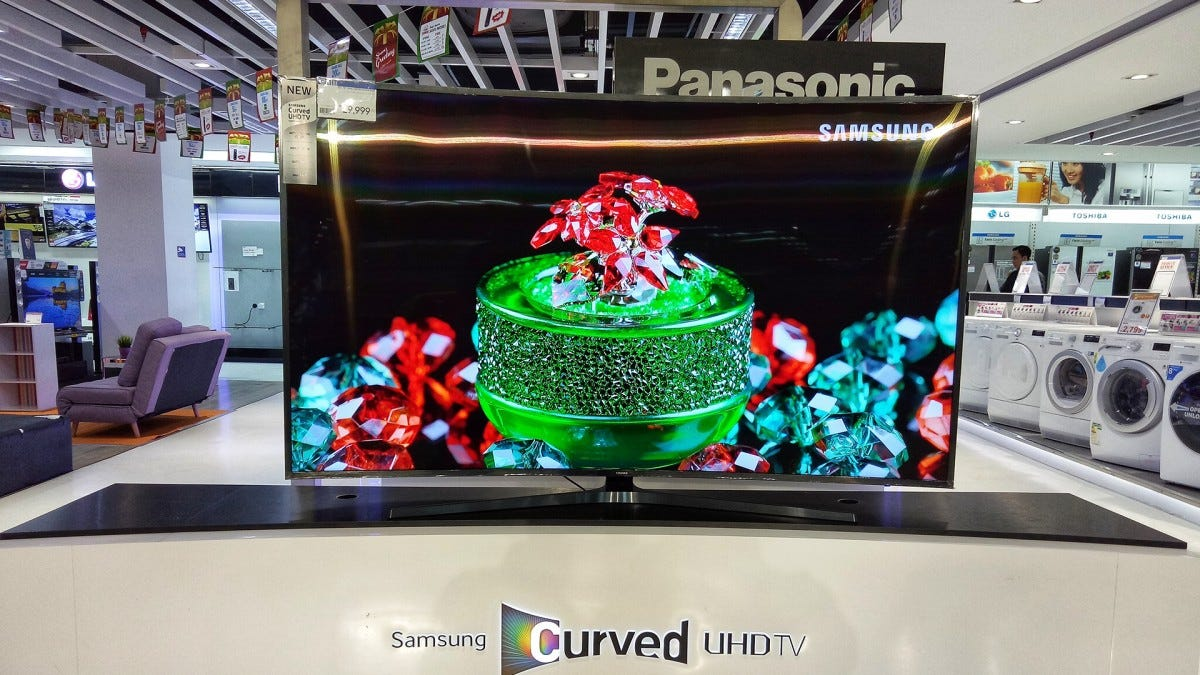 A curved Samsung TV on the showroom floor.
