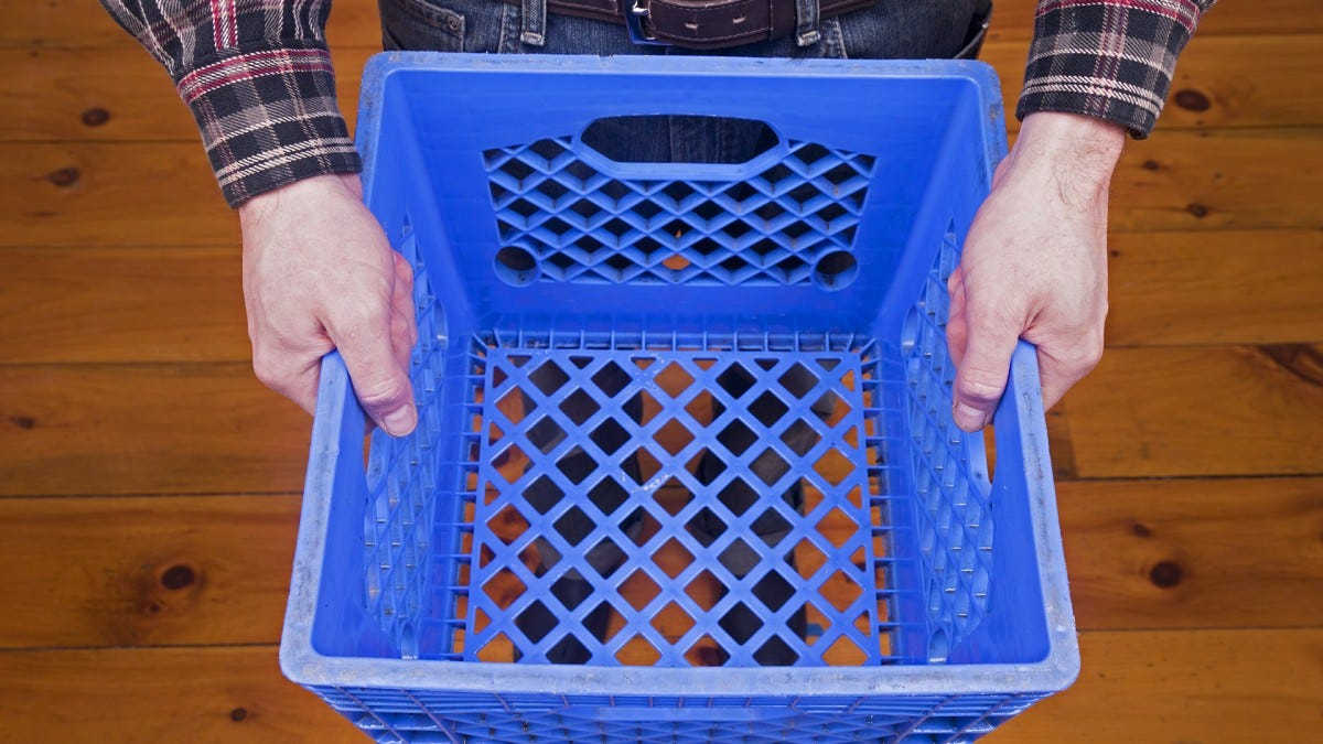 A man holding a plastic blue milk crate.