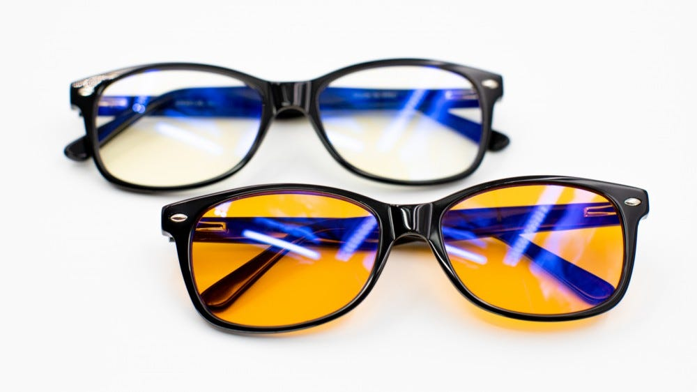 Two pairs of blue light blocking glasses against a white background