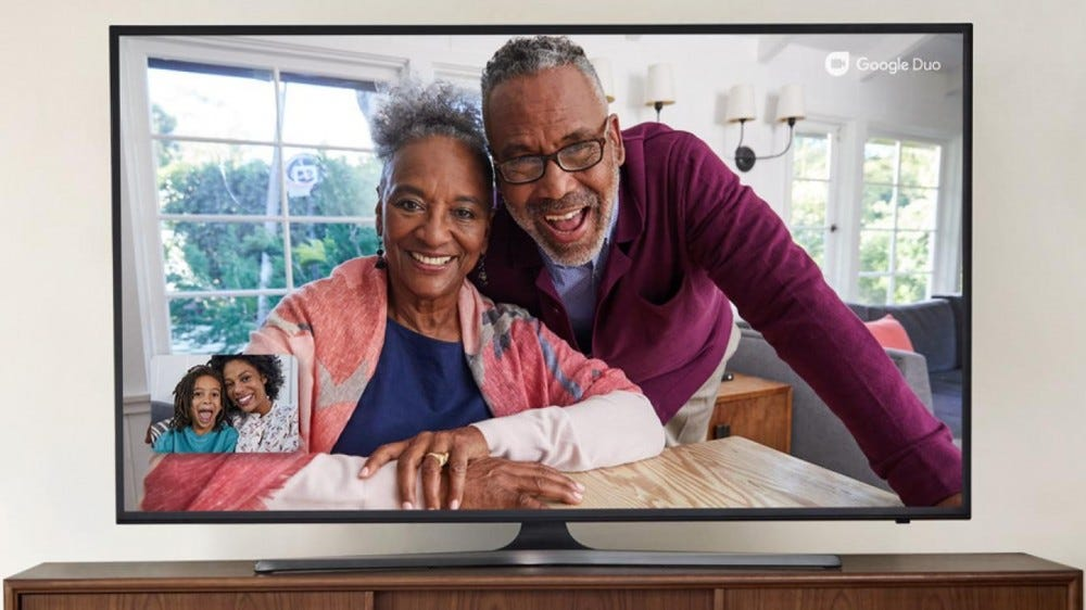 A couple talking to a family over a video call on their TV
