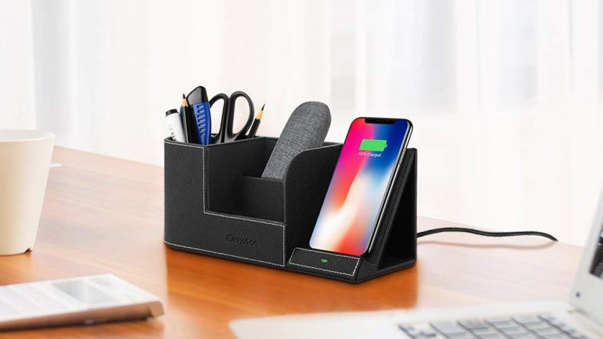 The EasyAcc Wireless Charger with Desk Organizer on a desk, filled with pencils, pens, a pair of scissors, a glasses case, and smartphone that's charging.