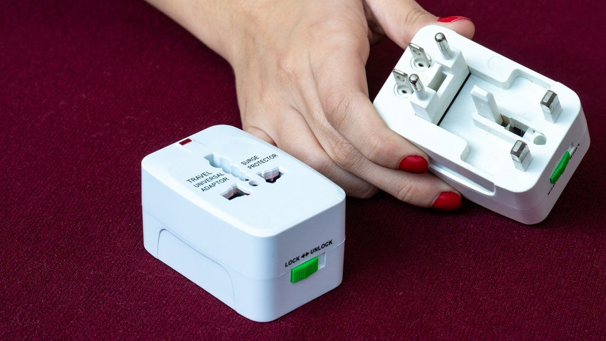 A woman examines a Type G plug adapter.