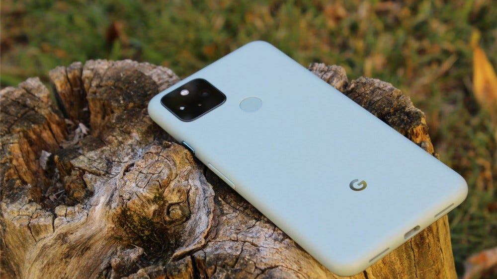The Sage Green Pixel 5 lying screen-down on a tree trunk