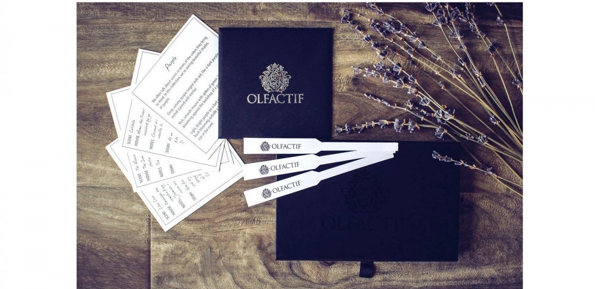 Olfactif fragrance sample box, with three fragrance sample sticks and the scent guides describing them spread out on top.
