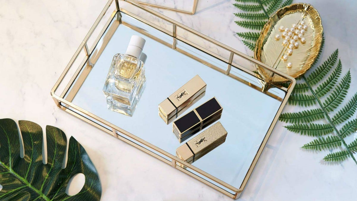 The PuTwo Tray Mirror holding a glass perfume bottle and three smaller perfumes.