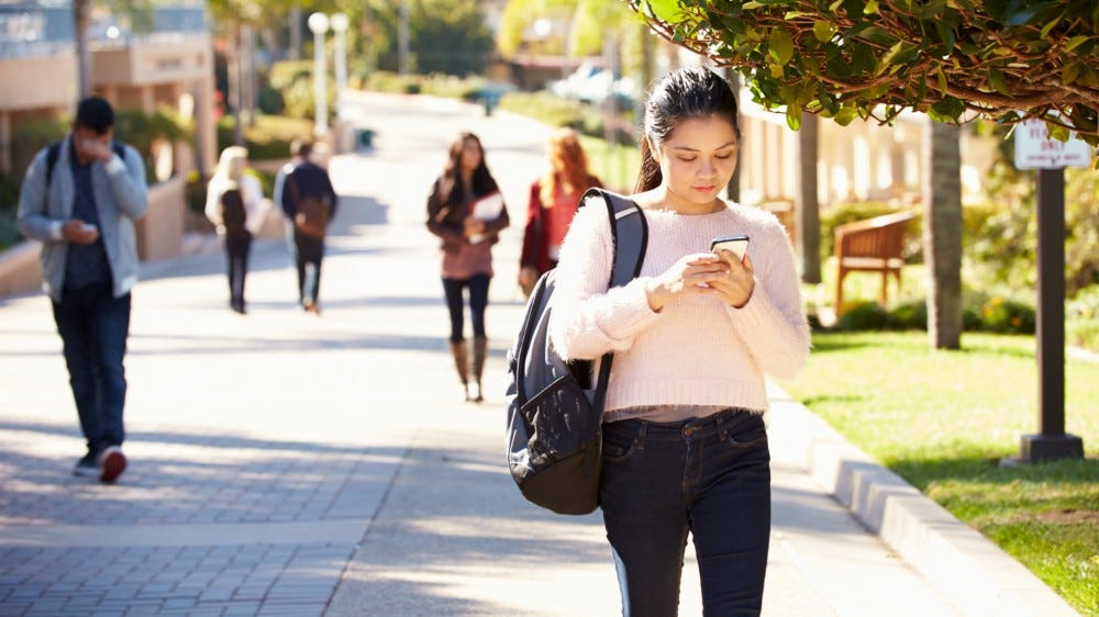 Students walking outdoors on university campus while using phone