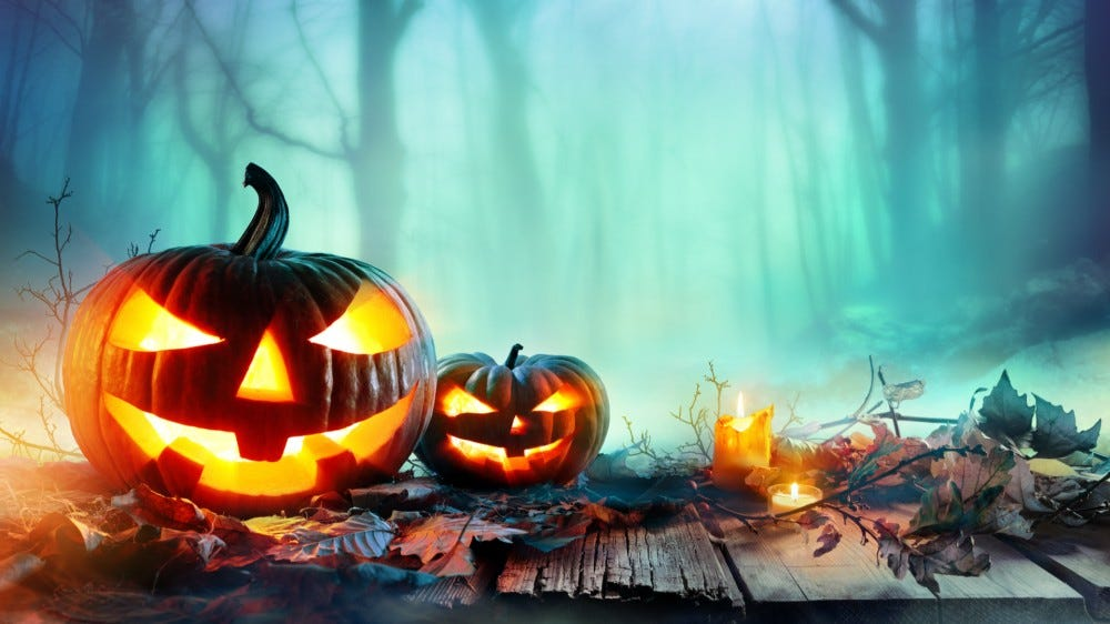 Carved pumpkins with lit candles in forest at night