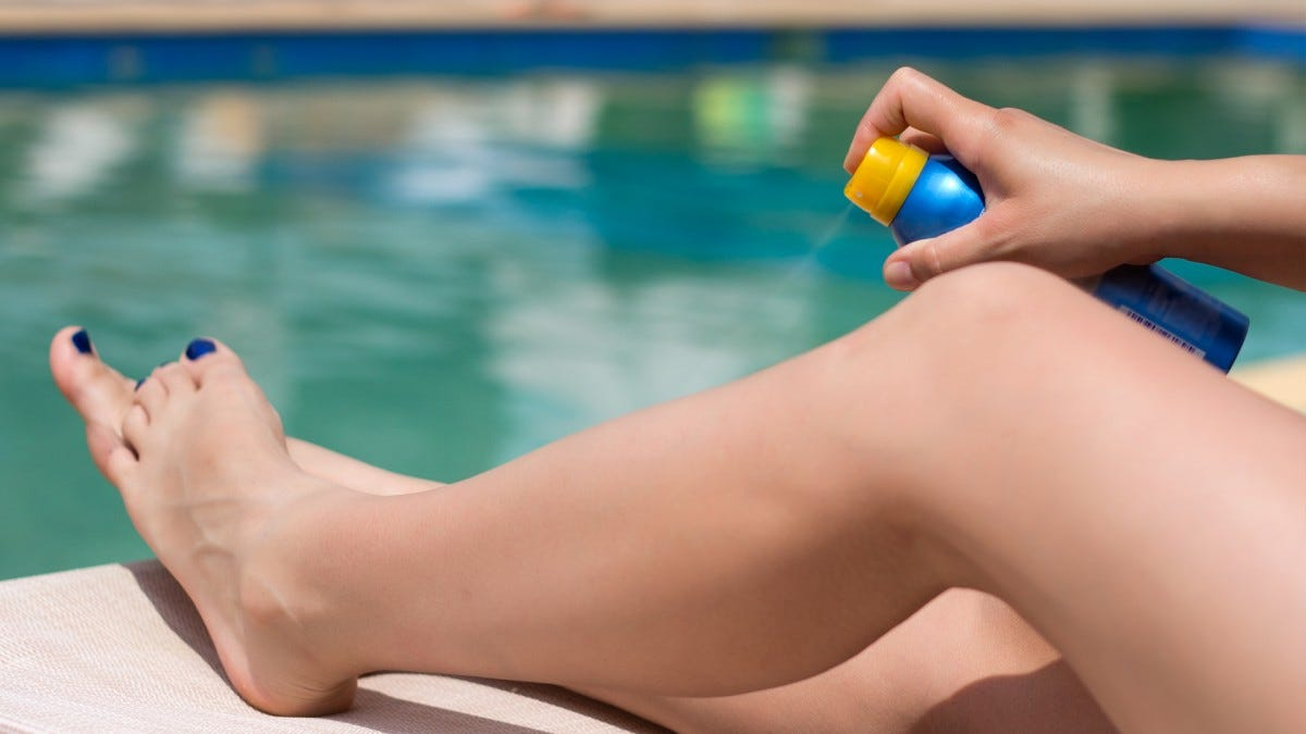 A woman's legs being sprayed with sunscreen.