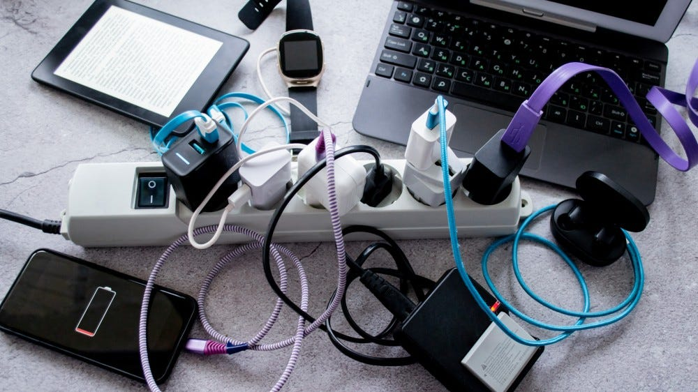 Gadgets with battery and cable accessories strewn across a surface
