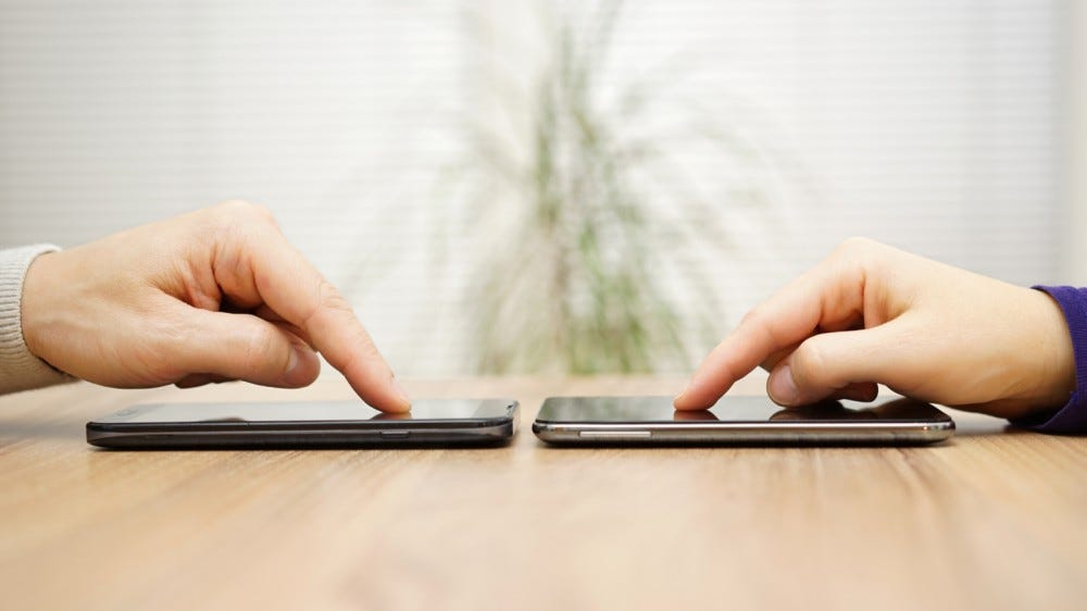 Two people are sharing files on their smartphones