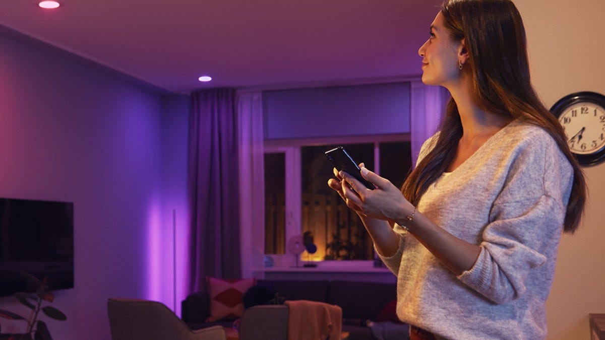 A women controls her new Philips Hue bulb through Bluetooth.