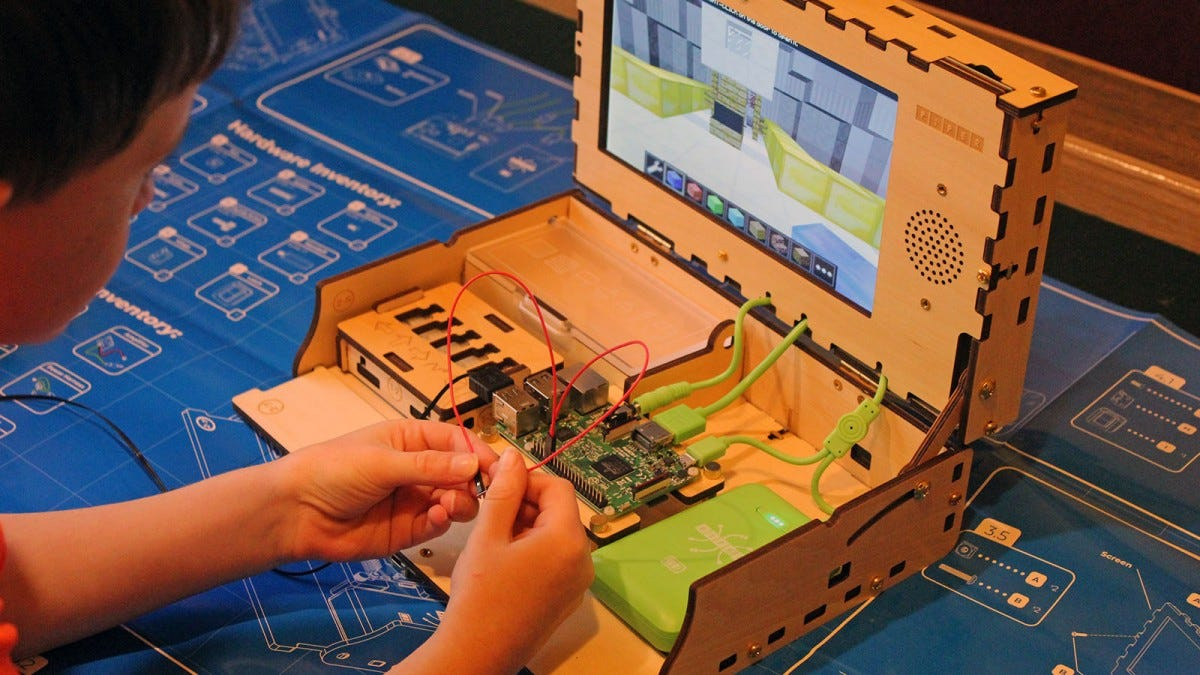 A boy connecting two wires to a Raspberry Pi and then tapping the ends together.
