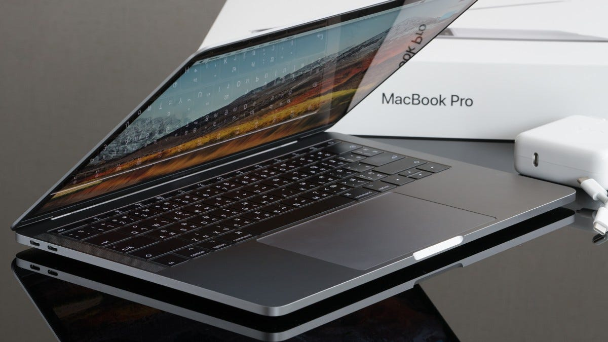 A MacBook Pro on a table next to its box.