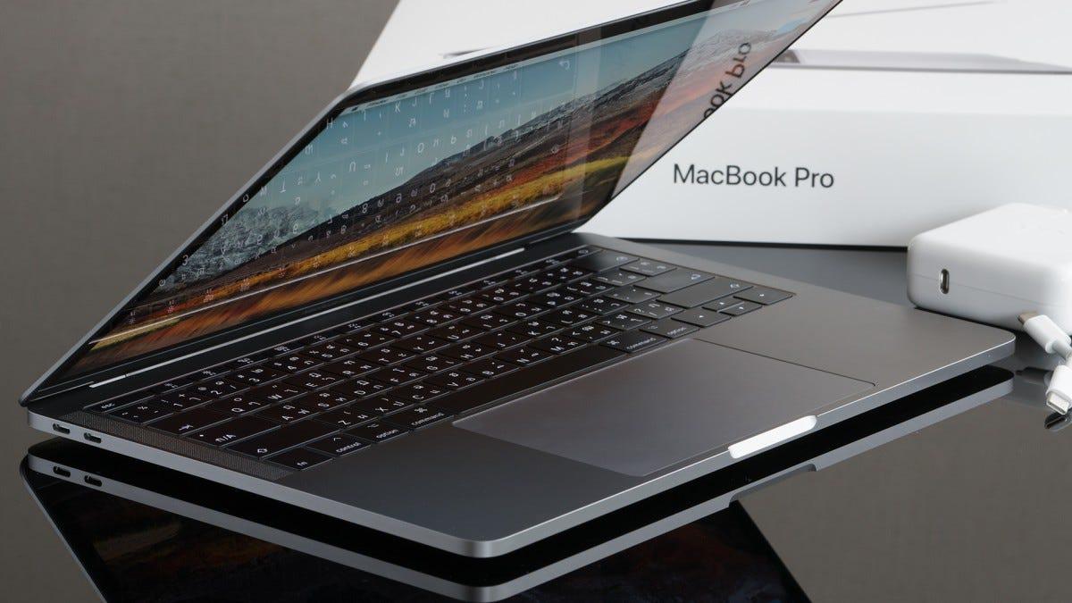 Un MacBook Pro su un tavolo accanto alla sua scatola.