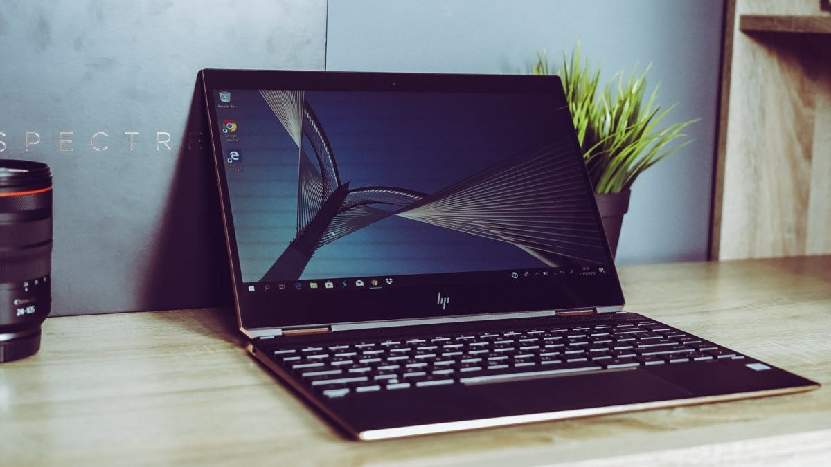 An HP Spectre x360 on a wood desk near a camera lens.