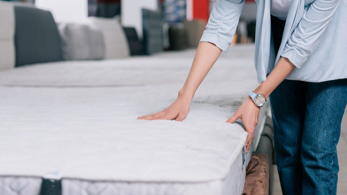 A woman checks a mattress' bounciness.