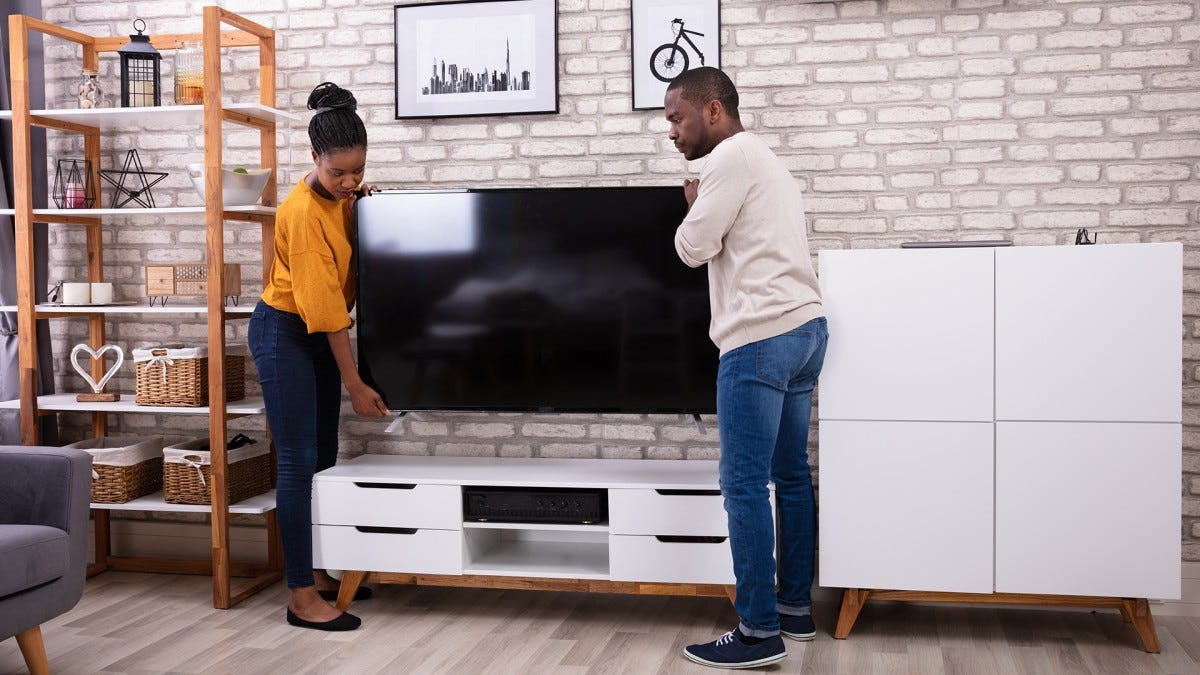 A young couple install a new TV in their house.