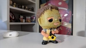 A sample picture from the Pixel 5: A Leatherface collectible on a white desk; AirPods and other memorabilia in the background