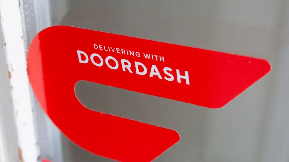The DoorDash logo on a glass door
