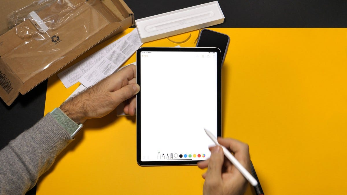 A man holding an iPad Pro and Apple pencil on a yellow background